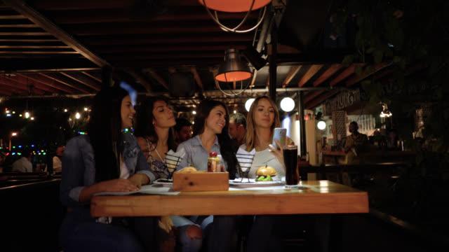 vídeos y material grabado en eventos de stock de grupo de amigas en un restaurante disfrutando de su comida y tomar un selfie - happy meal