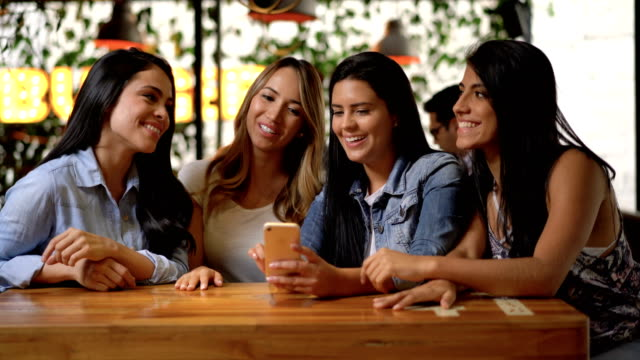 Group of female friends at a restaurant looking at photos gossiping