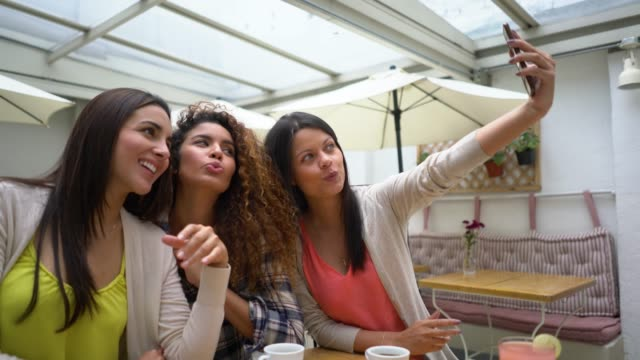 Group of female friends at a restaurant taking a selfie and making funny faces