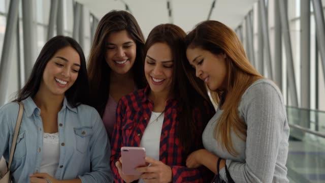 話をしながらスマート フォンでソーシャル メディアを見てショッピング モールで女友達のグループ - 買い物袋点の映像素材/bロール