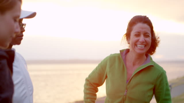 MS group of female friends laughing together after completing run at sunset
