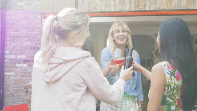 Group of female friends making a celebratory toast standing in garden.