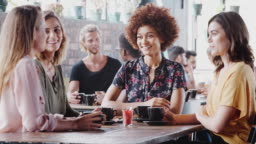 Group of female friends meeting and sitting around table talking in cafe - shot in slow motion