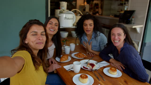 vídeos y material grabado en eventos de stock de grupo de amigas en una videollamada saludando a la cámara mientras hablan y sonríen en una cafetería - amistad femenina