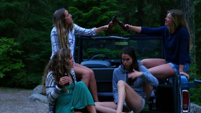 ms group of female friends toasting beers in back of convertible off road vehicle while camping - quattro persone video stock e b–roll