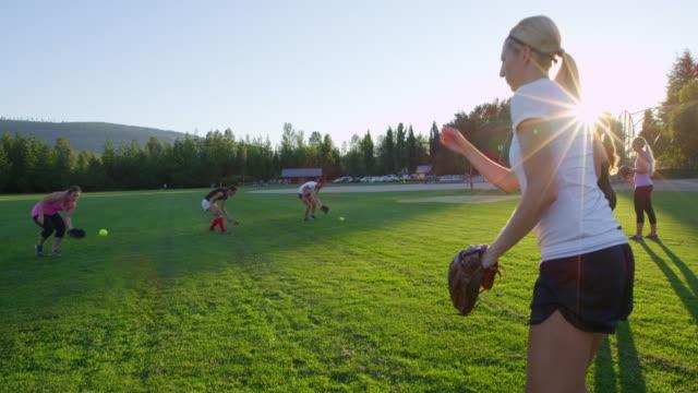 vídeos y material grabado en eventos de stock de ms slo mo group of female softball players practicing catching drills on field on summer evening - sófbol