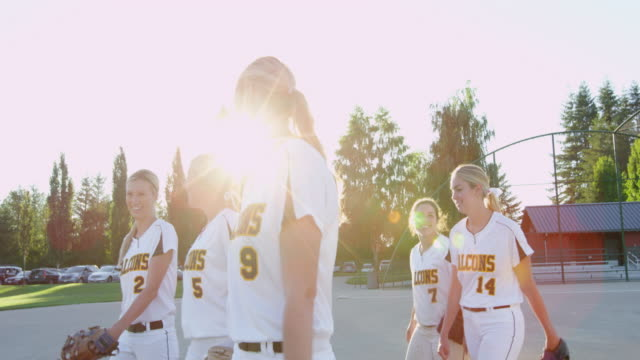 MS SLO MO Group of female softball teammates walking off of field together after evening game