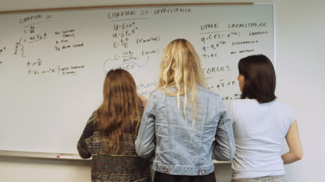 group of female students writing on chalk board - mathematics stock videos and b-roll footage