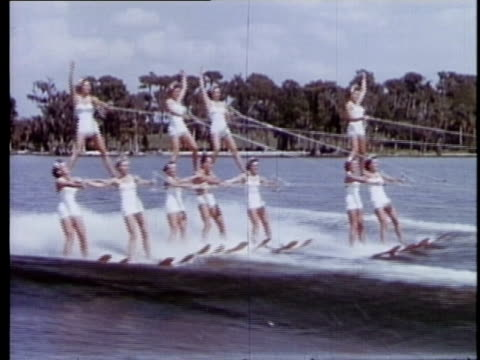 vidéos et rushes de 1957 ws group of female water skiers in pyramid formation with man at center/ cypress gardens, florida - homme dans un groupe de femmes
