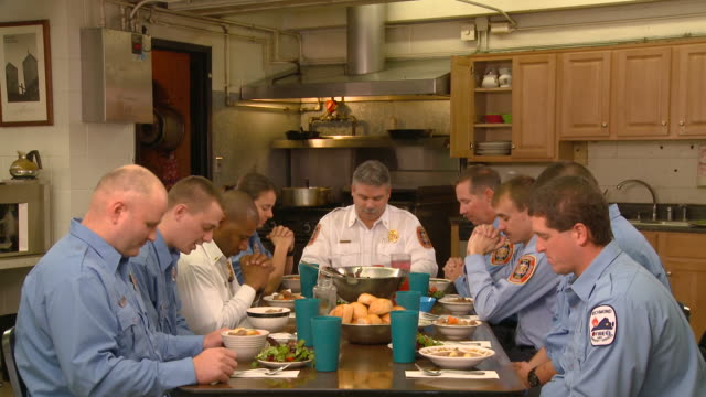 ms td group of fire fighters praying before eating in fire station kitchen/ richmond,  virginia - fire station stock videos & royalty-free footage