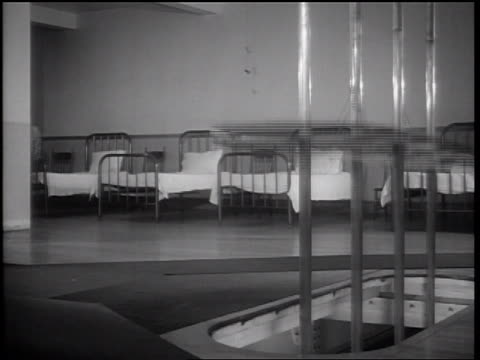 vidéos et rushes de b/w 1936 group of firemen running + sliding down set of poles through floor - poteau d'appui