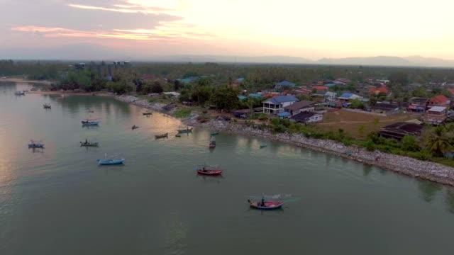 Groep visserij boten afgemeerd in zee met prachtige zonlicht, luchtfoto video