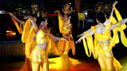 group of five asian women actresses in traditional thai yellow costumes dancing