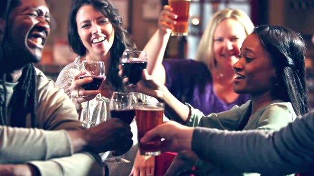 group of five multi-ethnic people drinking in bar - etnia video stock e b–roll