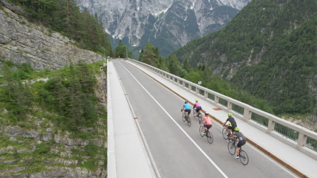 aerial group of five road cyclists riding across a bridge high in the mountains - weekend activities stock videos & royalty-free footage