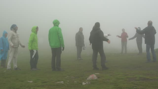 group  of followers of the universal white brotherhood practicing breathing exercises and paneurhythmy dance in rila mountain in a foggy weather - new age stock videos and b-roll footage