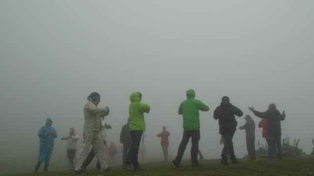 group  of followers of the universal white brotherhood practicing breathing exercises and paneurhythmy dance in rila mountain in a foggy weather - new age stock videos & royalty-free footage