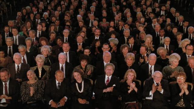 vídeos y material grabado en eventos de stock de a group of formally dressed people sit in an audience. - audiencia