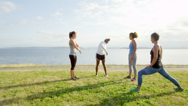 MS group of four female friends stretching on grass before run