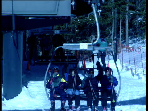 Group of four get onto ski-lift wearing ski wear and carrying skis. Bars come down as camera zooms out and lift travels overhead against blue sky. Winter Park Colorado blue filter applied