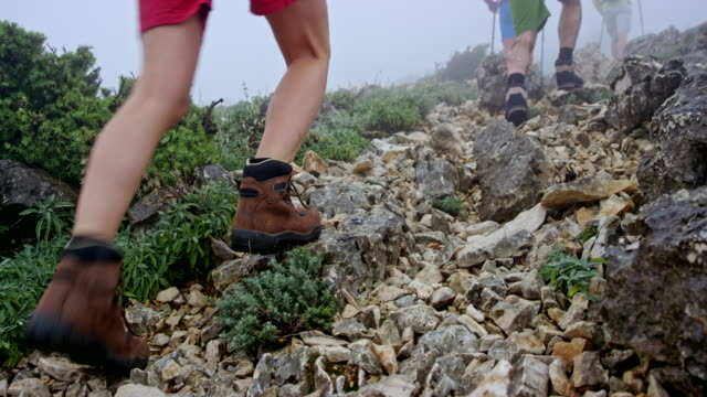 group of four hikers walking up the mountain in fog - climbing equipment stock videos and b-roll footage
