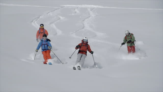 group of four skiers skiing on powder snow covered mountains. - slow motion - skifahren stock-videos und b-roll-filmmaterial