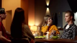 Group of four young friends, two couples, sitting at table in domestic kitchen and talking over dinner. Selective focus of tired young woman yawning