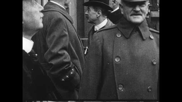 Group of French officials standing in front of building / Gen John J Pershing Commander of American Expeditionary Forces standing next to French...