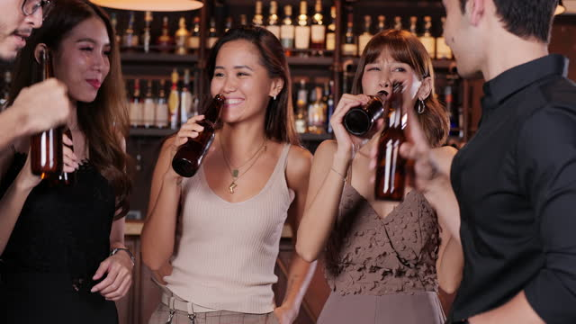 group of friend dancing with smile together at bar counter. they having enjoy with night party. party, enjoyment, friendship and lifestyle concept. - beer bottle stock videos & royalty-free footage