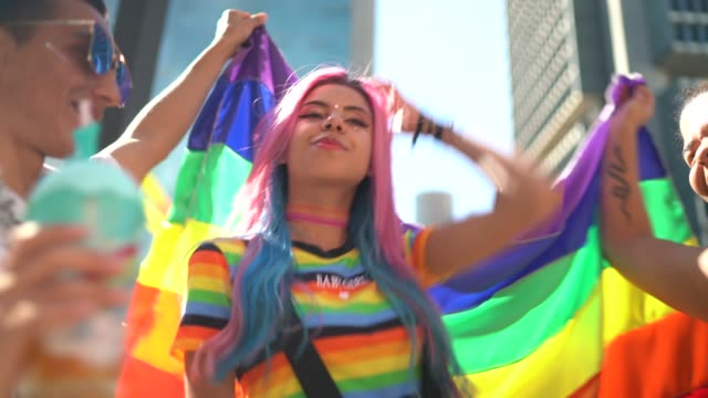 group of friend waving a rainbow flag and having fun during lgbtqi parade - pride stock videos & royalty-free footage