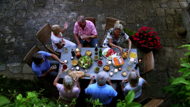 group of friends al fresco dining - terza età video stock e b–roll