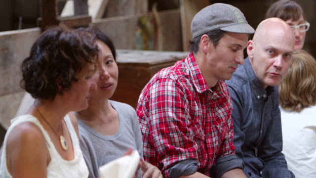vidéos et rushes de ms pan group of friends and family in discussion during summer dinner party in rustic building - groupe moyen de personnes
