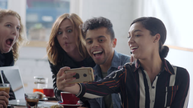 stockvideo's en b-roll-footage met ms. group of friends around table pose for smartphone selfies in local coffee shop hangout. - zelfportret fotograferen
