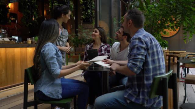 vídeos de stock e filmes b-roll de group of friends at a restaurant looking at the menu and ordering to friendly female waitress - empregada de mesa