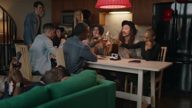 group of friends at kitchen table raise their glasses and cheers their drinks while young man looks at his smartphone on the couch. - beatnik stock videos & royalty-free footage