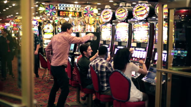 group of friends at slot machines cheers their drinks in las vegas casino - casino stock videos & royalty-free footage