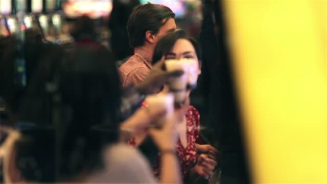 vídeos de stock, filmes e b-roll de group of friends at slot machines toast their drinks in las vegas casino - cassino