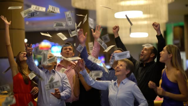 group of friends at the casino celebrating a big win throwing money to the air laughing - spending money stock videos & royalty-free footage