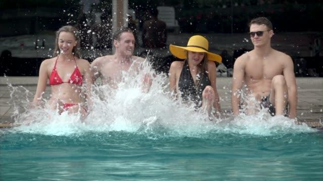 grupp vänner slå vatten i pool 4k - utebassäng bildbanksvideor och videomaterial från bakom kulisserna