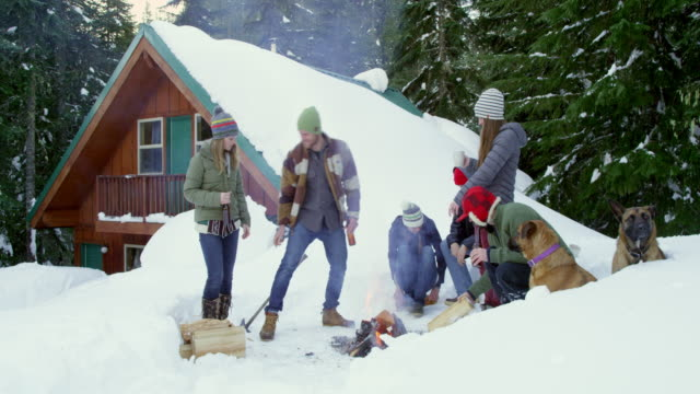 ms group of friends building fire in snow in front of cabin in woods. - cappotto invernale video stock e b–roll