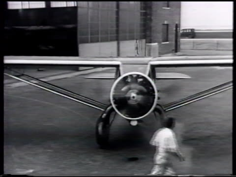 vidéos et rushes de group of friends by airplane outside hangar, man turning propeller, turning propellers, tracking aircraft taxiing, aircraft not stable, rocking side... - bercement