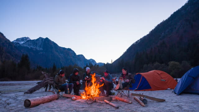 group of friends camping, sitting by the campfire - storytelling stock videos & royalty-free footage