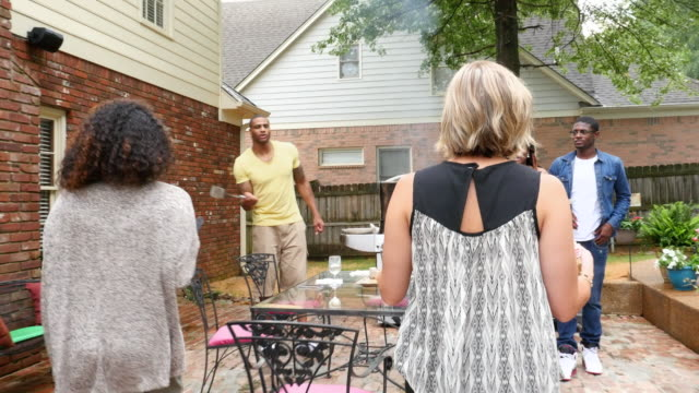 ms ts group of friends carrying food to table during outdoor dinner party on summer evening - courtyard stock videos & royalty-free footage