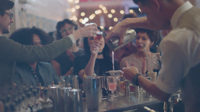 a group of friends celebrate and toast together at a bar after work - busy stock videos & royalty-free footage
