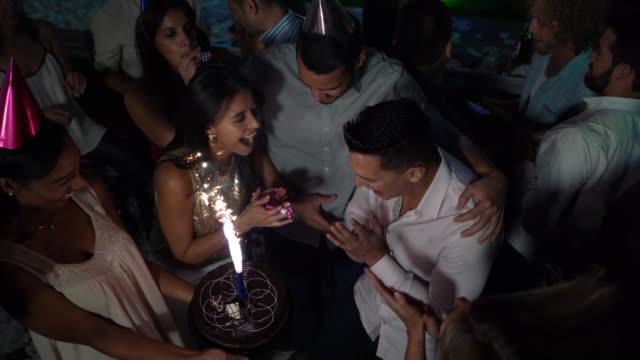 vidéos et rushes de groupe d'amis célébrant un anniversaire à un bar avec un gâteau d'anniversaire tout dansant et souriant - festivité