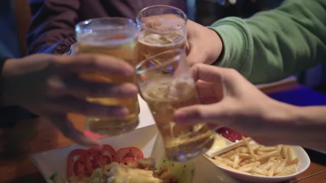 vídeos de stock, filmes e b-roll de grupo de amigos comemorando e brindando com cerveja no café - lanche