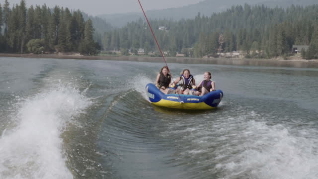 uhd 4k: group of friends cheerfully riding an inner tube together during summer vacation - tubing stock videos and b-roll footage