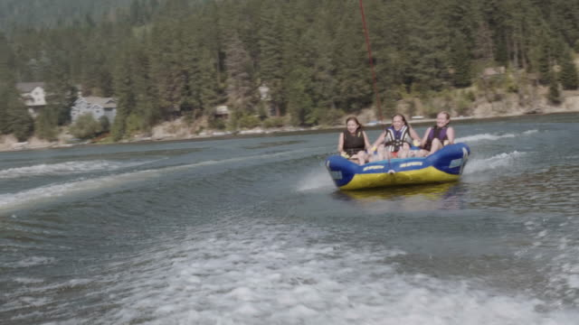 uhd 4k: group of friends cheerfully riding an inner tube together during summer vacation - rubber ring stock videos & royalty-free footage