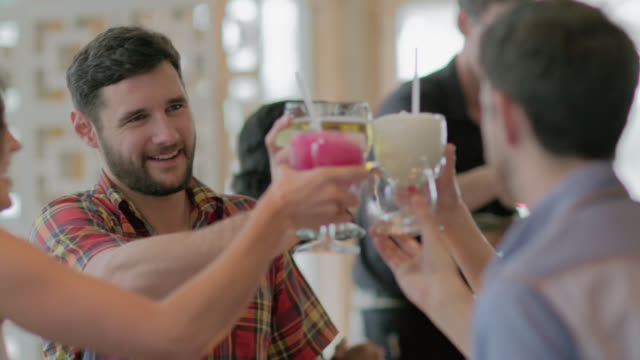 Group of friends cheers their drinks and clink glasses in restaurant