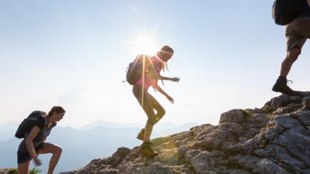 group of friends climbing mountain ridge to summit - achievement点の映像素材/bロール